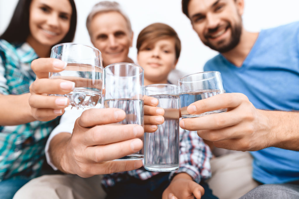 family drinking water smiling