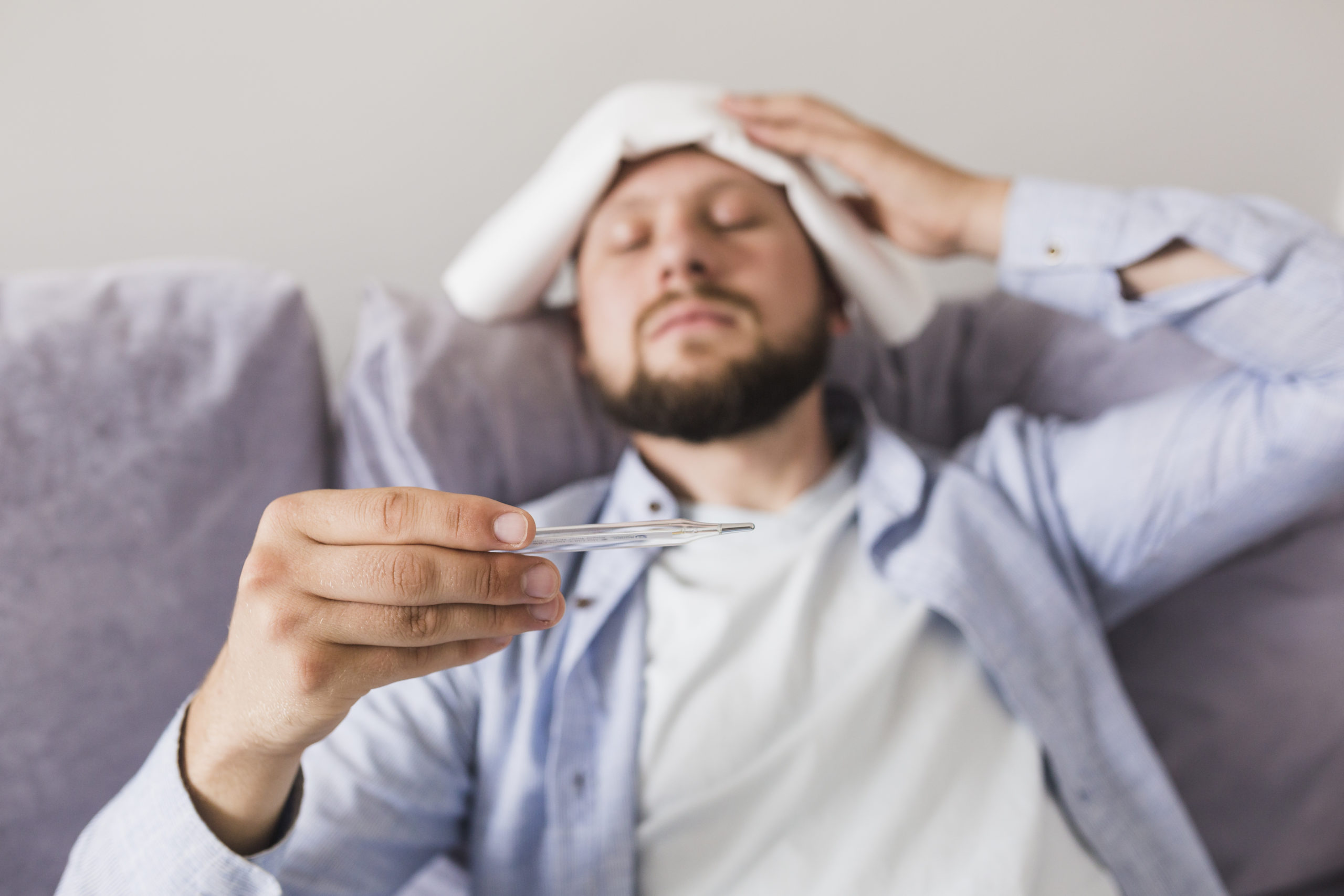 Man looking at thermometer with towel on forehead